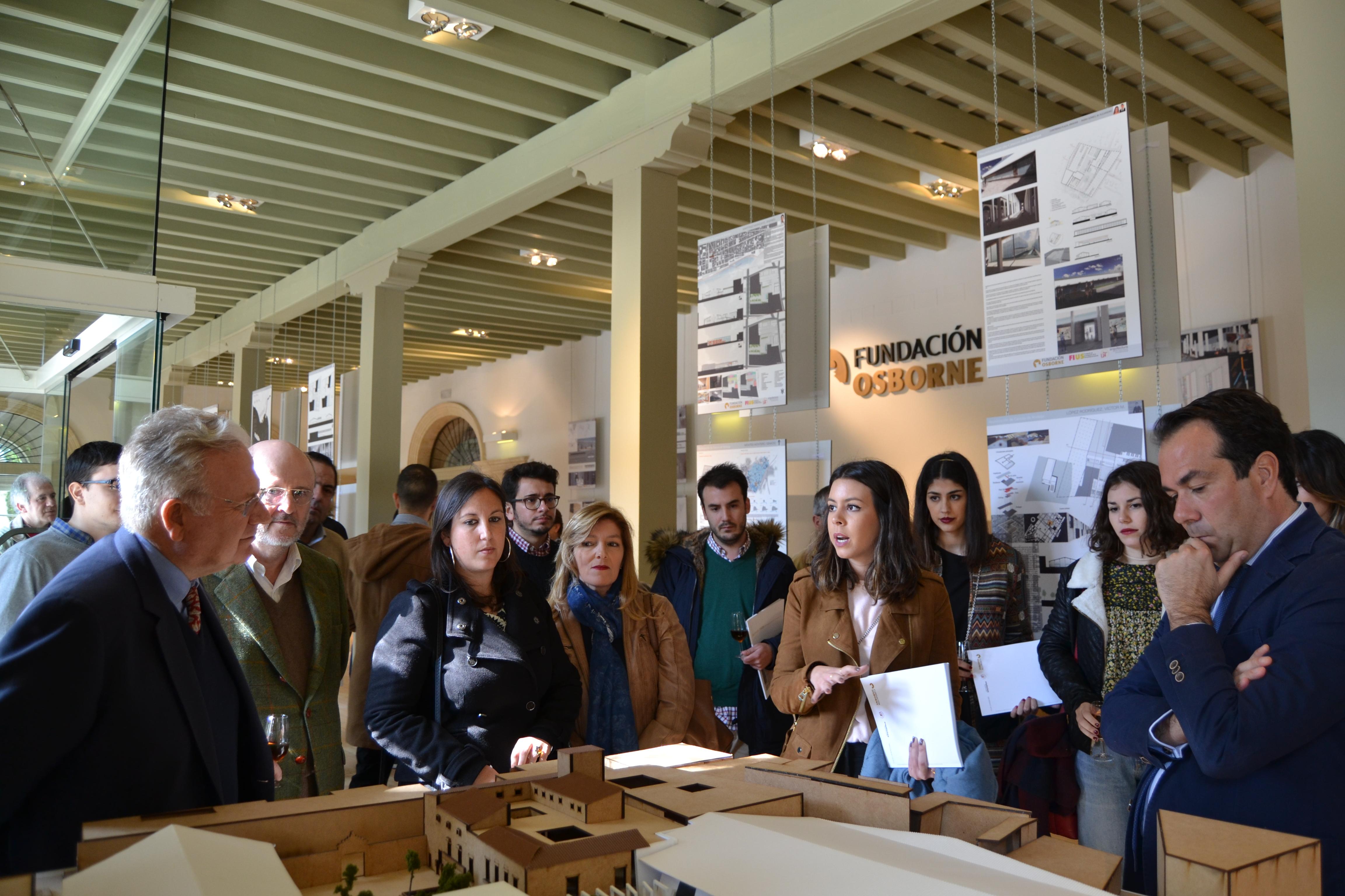 Aparece una alumna de Arquitectura presentando la maqueta de su proyecto, al presidente de la Fundación y a los medios de comunicación entre otros