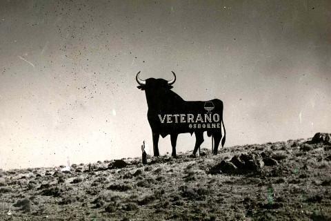 Foto en sepia del primer toro que se colocó en 1957 en Cabanillas de La Sierra, Madrid. Junto a nuestra valla publicitaria del Toro de Osborne aparece, Rafael Osborne McPherson